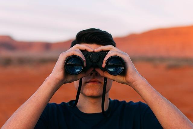望遠鏡で遠くを見る人